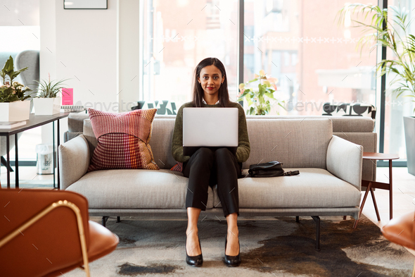 Portrait Of Businesswoman Sitting On Sofa Working On Laptop At Desk In Shared Workspace Office - Stock Photo - Images