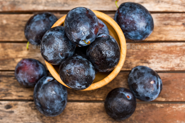 Fresh ripe plums in wooden bowl top view - Stock Photo - Images