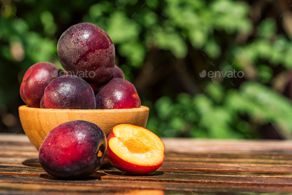 Pluot, mix of plum and apricot in wooden bowl - Stock Photo - Images