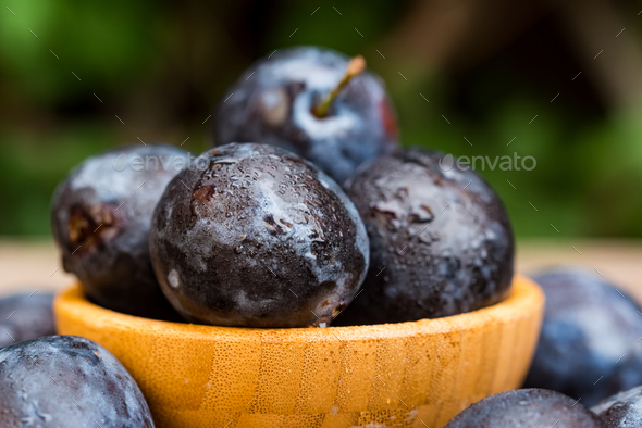 Fresh ripe plums in wooden bowl close - Stock Photo - Images