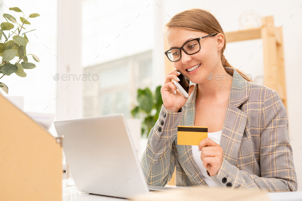 Pretty well-dressed businesswoman talking to online shop manager on mobile phone - Stock Photo - Images