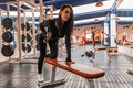 Young beautiful woman trains biceps in modern gym - PhotoDune Item for Sale