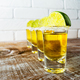 Tequila shots on the rustic wooden table and painted brick wall. - PhotoDune Item for Sale