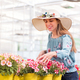 Happy young woman selecting a petunia plant - PhotoDune Item for Sale