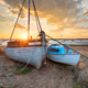 Stunning sunset over old fishing boats on the shore at West Mers - PhotoDune Item for Sale