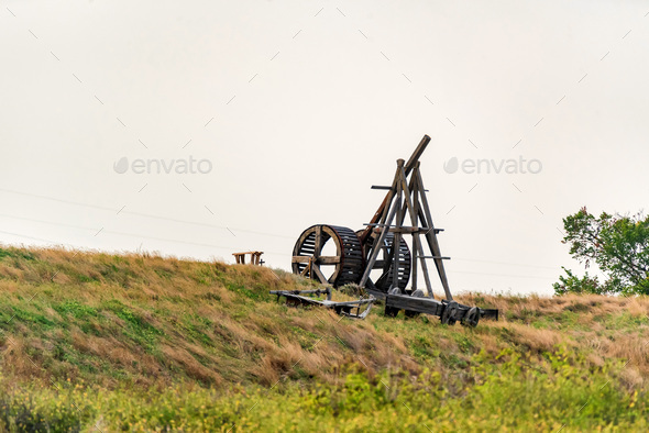 Old wooden catapult against grey sky background - Stock Photo - Images