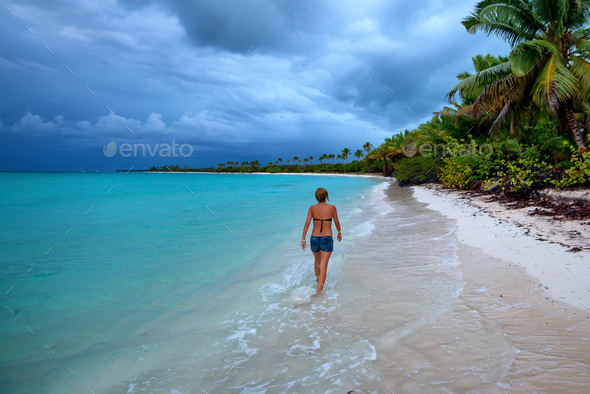 Teenage girl walks on beach in Dominican Republic - Stock Photo - Images