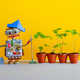 Robot gardener with bucket shovel rake and sprouts of wild strawberries in clay flower pots. - PhotoDune Item for Sale