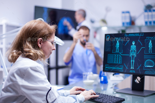 Woman working with computer in the office of a science laboratory - Stock Photo - Images
