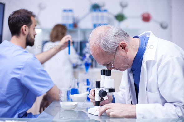 Senior technician making a discovery while working on microscope - Stock Photo - Images