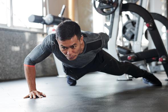 Sportsman doing one arm push-ups - Stock Photo - Images