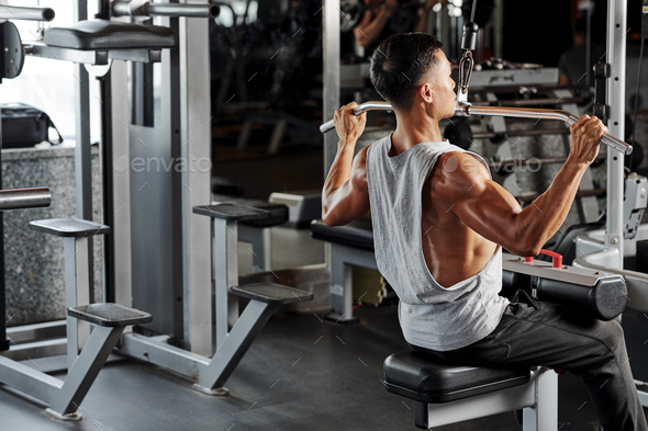 Man exercising in pull down machine - Stock Photo - Images