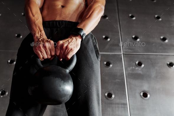 Strong man lifting kettlebell - Stock Photo - Images