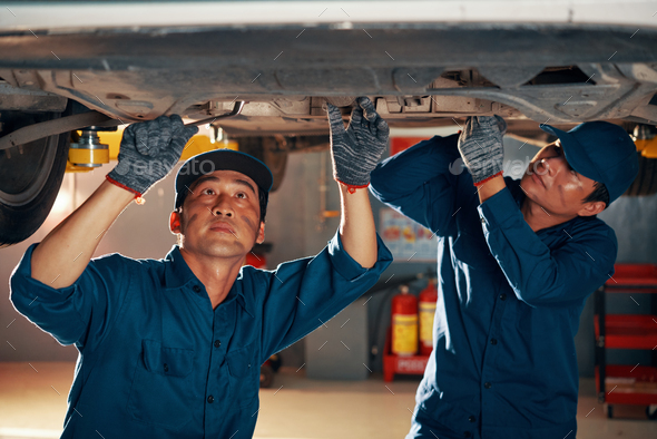 Mechanics attaching front car suspention - Stock Photo - Images