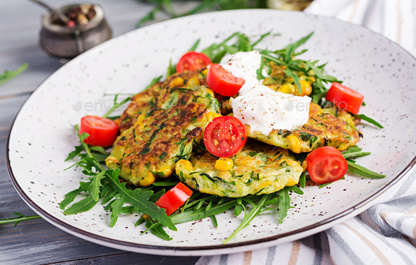 Zucchini pancakes with corn and sour cream served arugula, tomatoes salad. - Stock Photo - Images