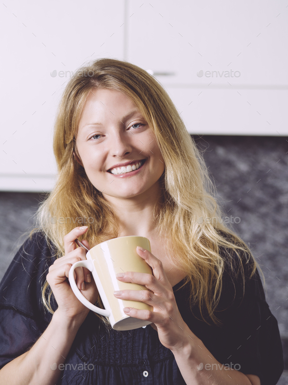 Beautiful blond having coffee in her kitchen - Stock Photo - Images