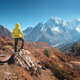 Sporty man on the stone is looking on snow covered mountains - PhotoDune Item for Sale