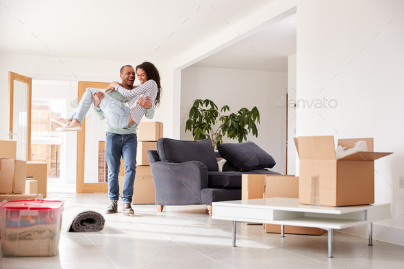 Man Carrying Woman Over Threshold Of New Home On Moving Day - Stock Photo - Images