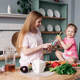 Happy woman making lunch from vegetables together with kid - PhotoDune Item for Sale