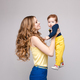 Young and fit woman in casual clothes holding little kid - PhotoDune Item for Sale