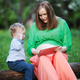 Pregnant mother with little son using touch pad in the park - PhotoDune Item for Sale