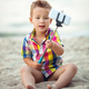 Child with phone and selfie stick on the beach - PhotoDune Item for Sale