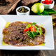 Beef carpaccio on white plate, wooden background. Close up. - PhotoDune Item for Sale