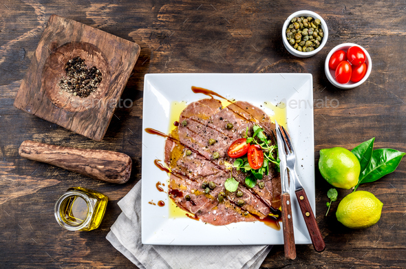 Raw BEEF CARPACCIO on white plate, wooden background, top view - Stock Photo - Images
