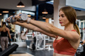 Beautiful young woman trains deltoid in gym - PhotoDune Item for Sale