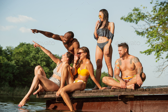 Group of friends splashing water and laughting on the pier on river - Stock Photo - Images