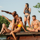 Group of friends splashing water and laughting on the pier on river - PhotoDune Item for Sale