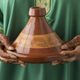 Moroccan woman with henna painted hands holding a tagine - PhotoDune Item for Sale