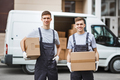 Two young handsome smiling workers wearing uniforms are standing next to the van full of boxes - PhotoDune Item for Sale