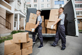 Two young handsome smiling workers wearing uniforms are unloading the van full of boxes. The block - PhotoDune Item for Sale