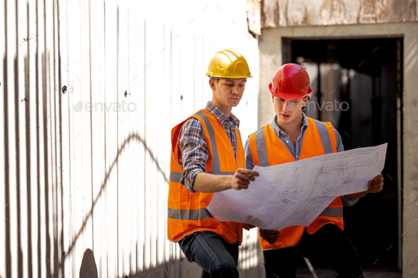 Structural engineer and construction manager dressed in work clothes and hard bats explore - Stock Photo - Images