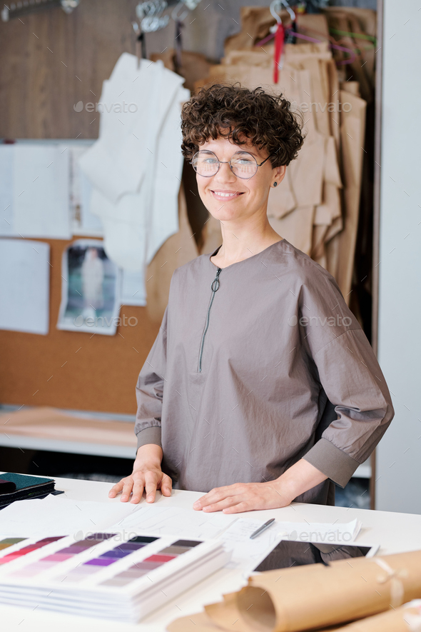 Happy Young Fashion Designer Looking At You By Workplace Stock Photo By Pressmaster