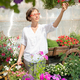 Young woman with basket of fresh flowers standing by flowerbed - PhotoDune Item for Sale
