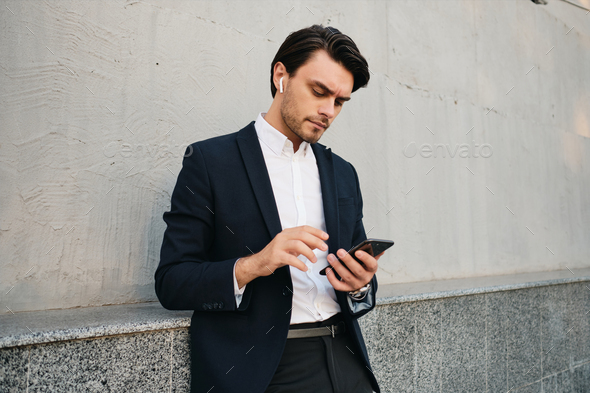 Young serious in classic suit with wireless earphones thoughtfully using cellphone outdoors - Stock Photo - Images