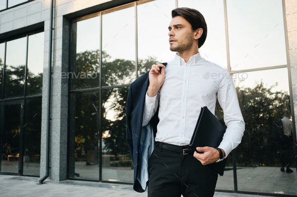 Young handsome businessman in white shirt holding jacket on shoulder thoughtfully looking aside - Stock Photo - Images