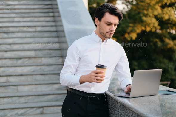 Young businessman holding cup of coffee to go thoughtfully working on laptop in city park - Stock Photo - Images
