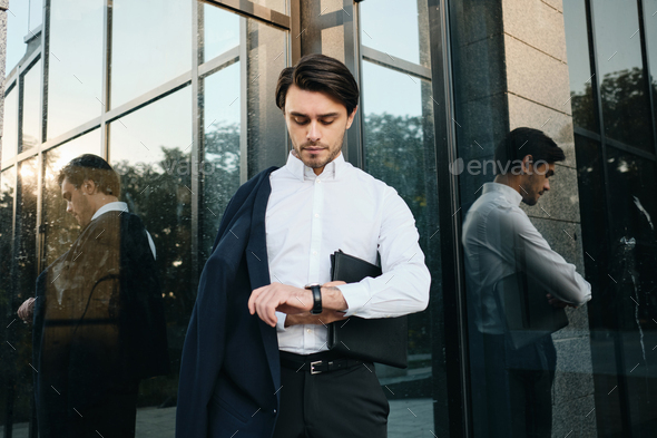 Young businessman with bag for documents thoughtfully looking on watch with over glass building - Stock Photo - Images
