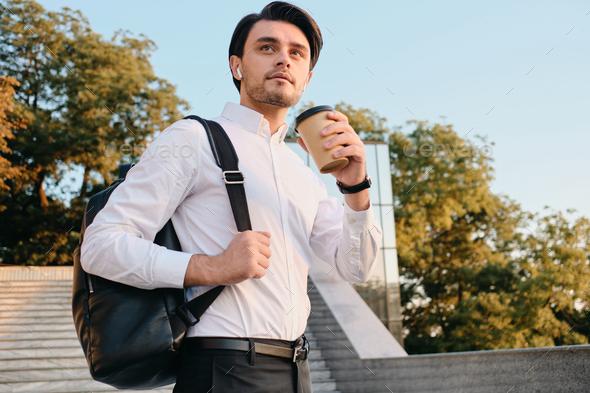 Attractive man in shirt drinking coffee carrying backpack and dreamily looking aside on city stairs - Stock Photo - Images