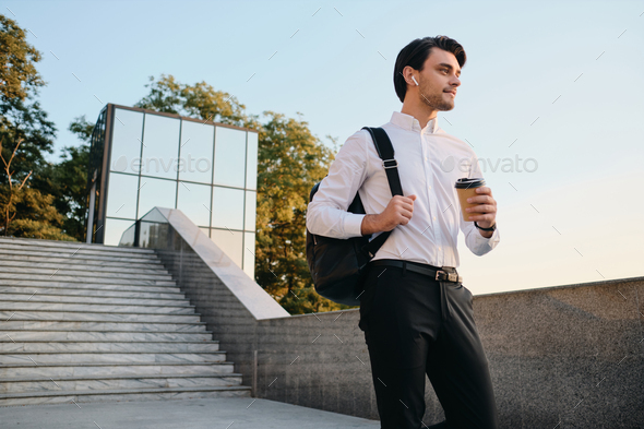 Young smiling man with backpack in white shirt drinking coffee dreamily walking in city park - Stock Photo - Images
