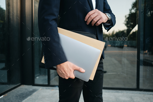Close up man in classic black suit standing outdoor holding laptop and big envelope in hand - Stock Photo - Images
