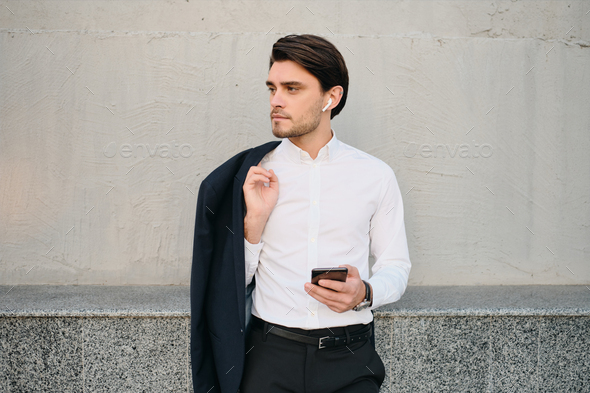 Young man in white shirt with jacket on shoulder using earphones and cellphone over gray wall - Stock Photo - Images