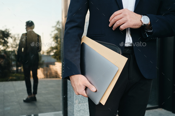 Close up of man in classic suit and watch holding laptop and big envelope reflecting in window - Stock Photo - Images