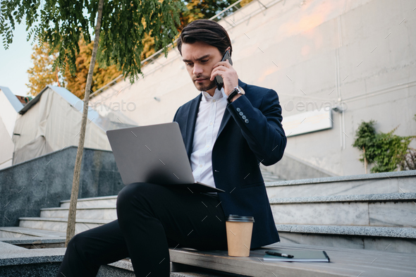 Young man in suit sitting on bench drinking coffee and thoughtfully talking on cellphone into laptop - Stock Photo - Images