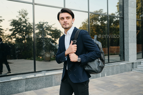 Young man in classic suit with earphones and backpack curiously looking aside walking office centre - Stock Photo - Images