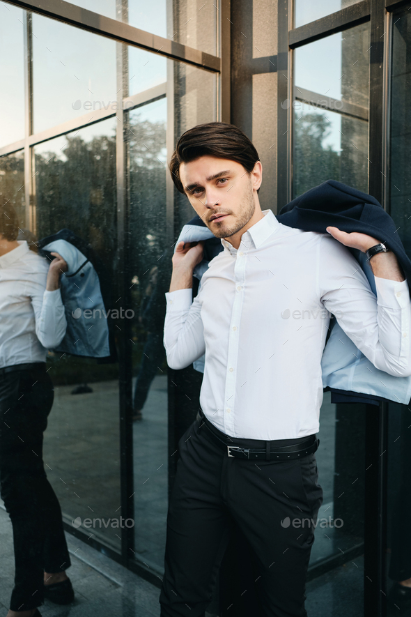 Young attractive man putting on classic jacket thoughtfully looking in camera near office centre - Stock Photo - Images