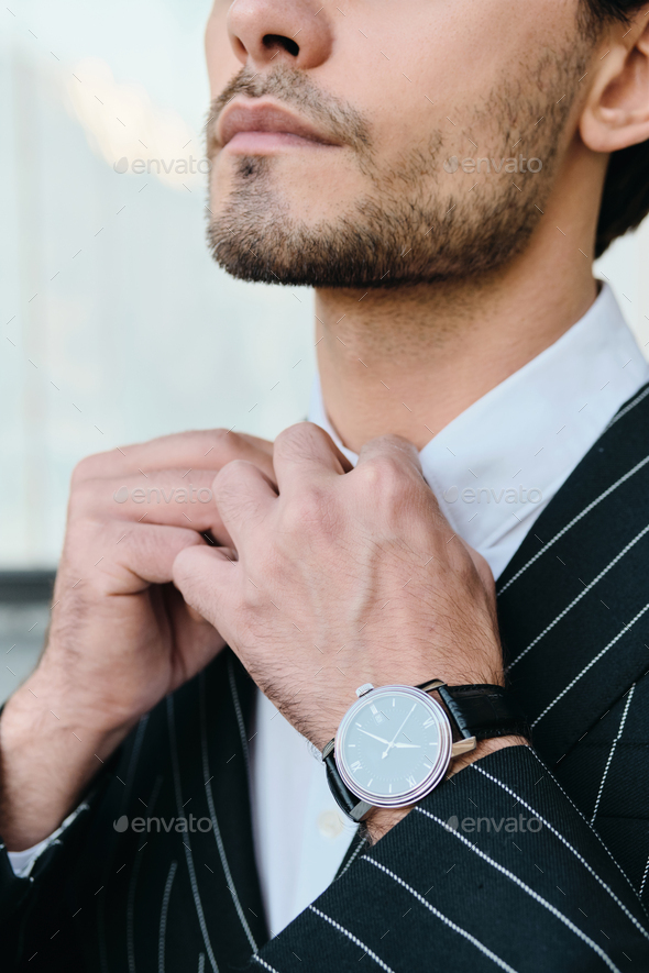 Close up bearded man in white shirt and classic striped jacket with watch on city street - Stock Photo - Images